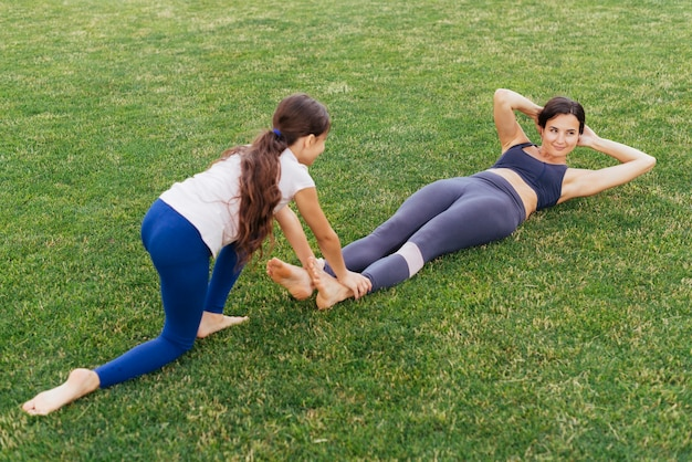 Mother and daughter exercising on green grass Free Photo