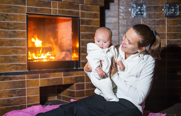 Mother and daughter at the fireplace. Premium Photo