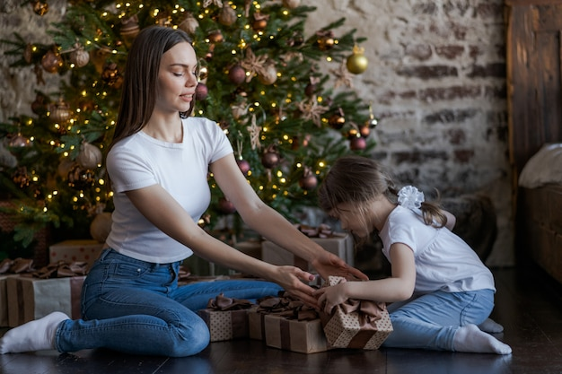 Mother and daughter in front of christmas tree, opening presents Premium Photo