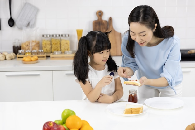 Mother and daughter helped to make breakfast in the kitchen at home Premium Photo
