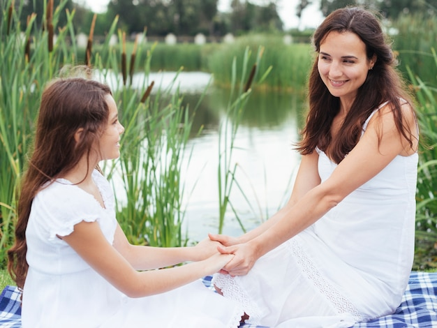 Mother and daughter holding hands by the lake Free Photo