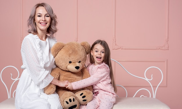 Mother and daughter holding teddy bear Free Photo