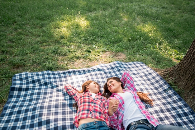 Mother and daughter holding their hand lying on blanket in park Free Photo