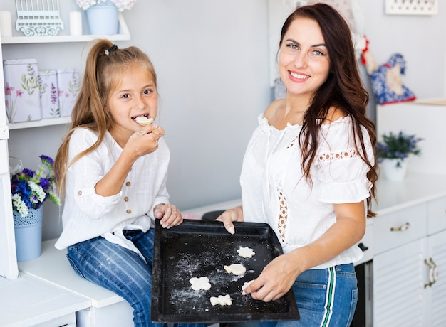 Mother and daughter holding tray with cookies Free Photo