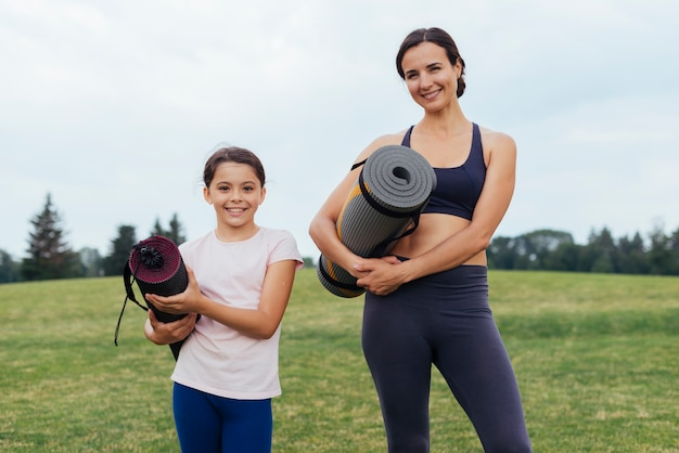 Mother and daughter holding yoga mats Free Photo