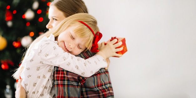 Mother and daughter hugging in front of christmas tree Free Photo
