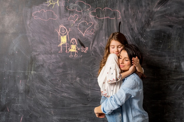 Mother and daughter hugging near chalkboard with drawing Free Photo