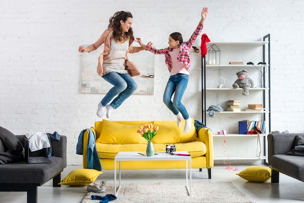 Mother and daughter jumping in the living room Free Photo