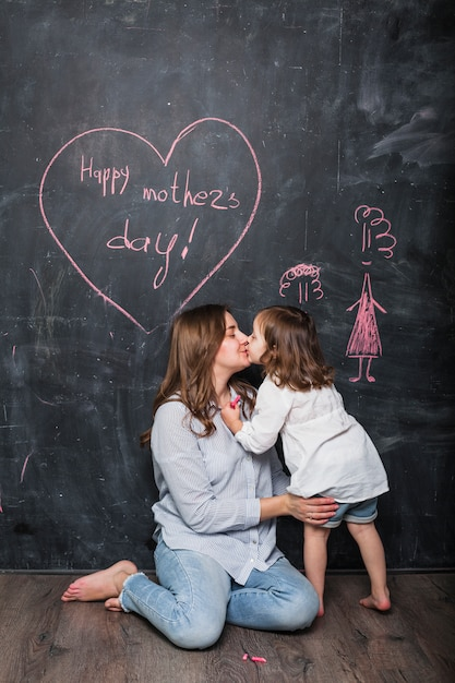Mother and daughter kissing near happy mothers day inscription Free Photo