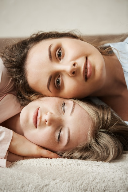 Mother and daughter looking like best friends. vertical shot of young attractive woman lying on head of another girl,  and smiling with relaxed and calm expression, feeling happy Free Photo
