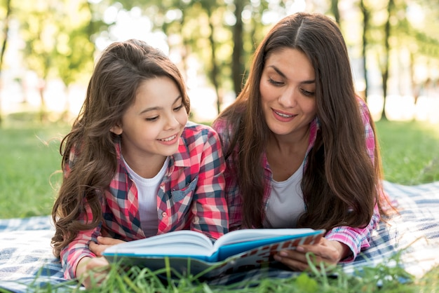 Mother and daughter lying on blanket reading book together Free Photo
