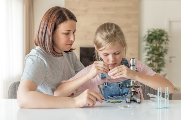 Mother and daughter make chemical experiments with microscope at home Premium Photo