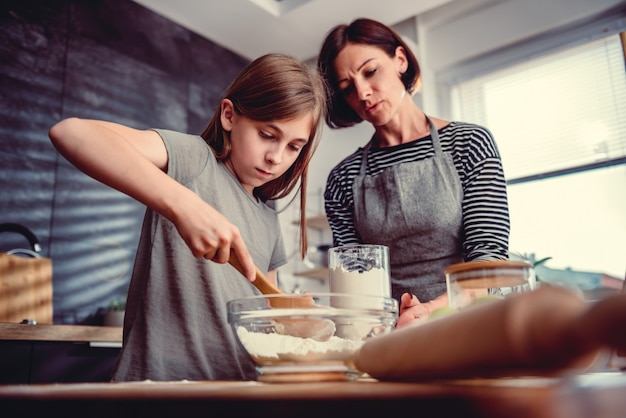 Mother and daughter making dough for apple pie Premium Photo