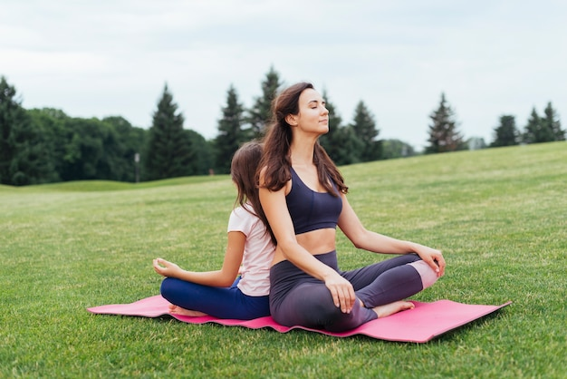 Mother and daughter meditating outdoors Free Photo