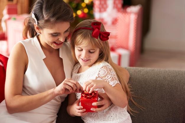 Madre e figlia che aprono il regalo avvolto Foto Gratuite