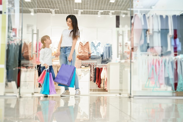 Mother and daughter posing near boutique with shopping bags. Free Photo