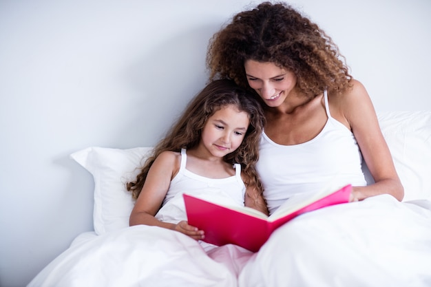 Mother and daughter reading book together on bed Premium Photo