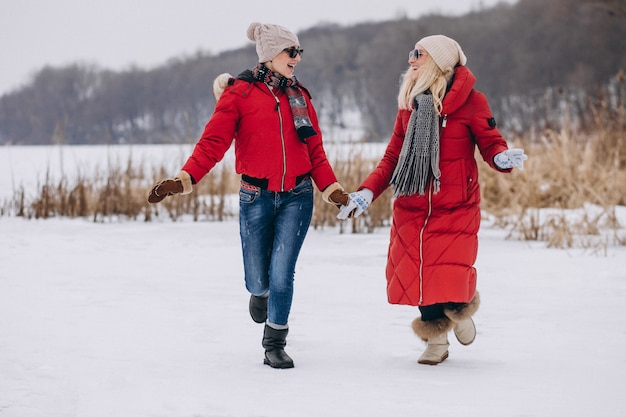 Mother and daughter running on lake in winter time Free Photo