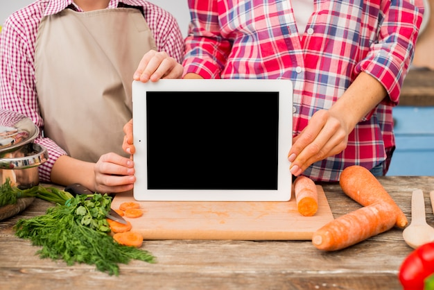 Mother and daughter showing blank screen digital tablet on chopping board with vegetables Free Photo