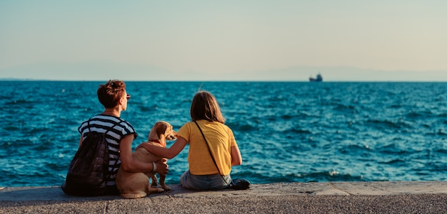 Mother and daughter sitting on the waterfront with dog Premium Photo