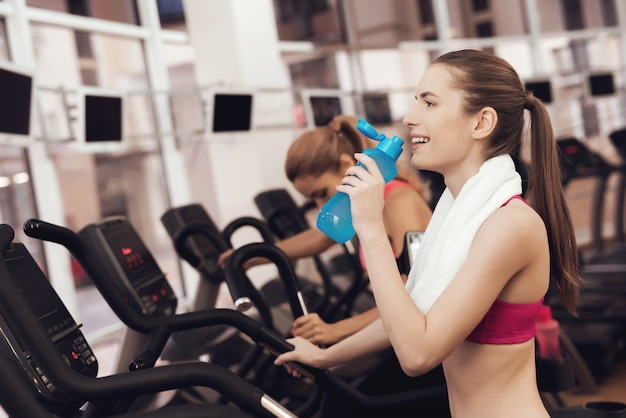 Mother and daughter in sportswear drinking water in gym Premium Photo