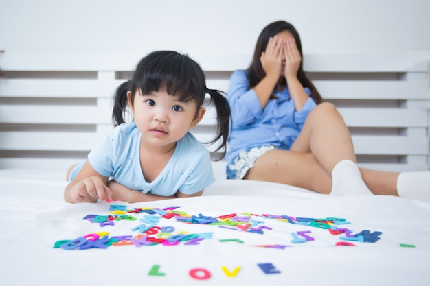Mother and daughter studying the alphabet Free Photo
