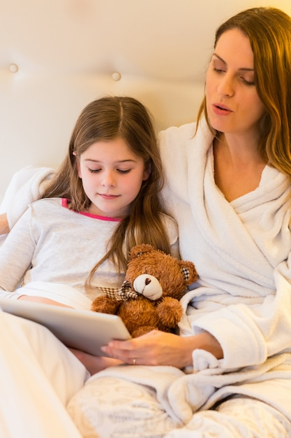 Mother and daughter using digital tablet in bedroom Free Photo