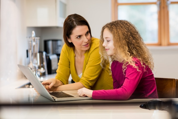 Mother and daughter using laptop in kitchen Free Photo