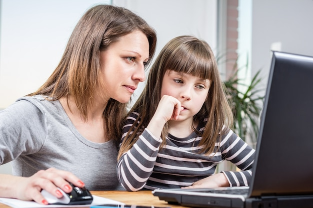 Mother and daughter using laptop Premium Photo