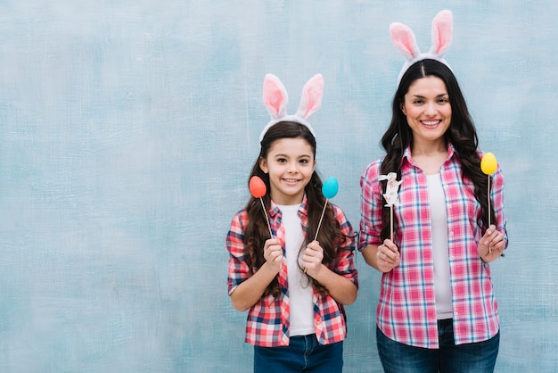 Mother and daughter wearing bunny ears holding easter eggs and bunny props Free Photo