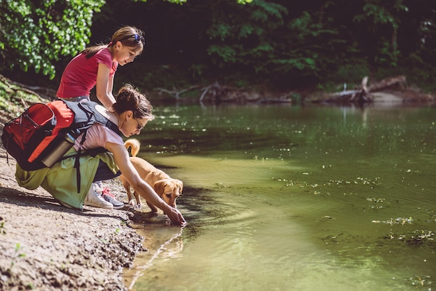 Mother and daughter with dog by the lake Premium Photo