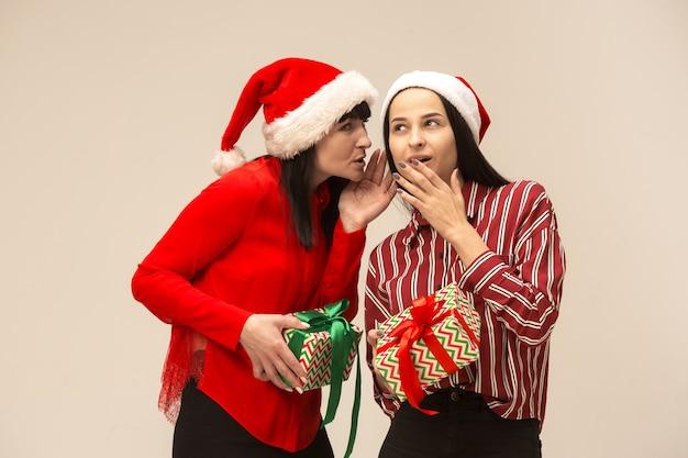 Madre e figlia con cappello da babbo natale e confezione regalo Foto Gratuite