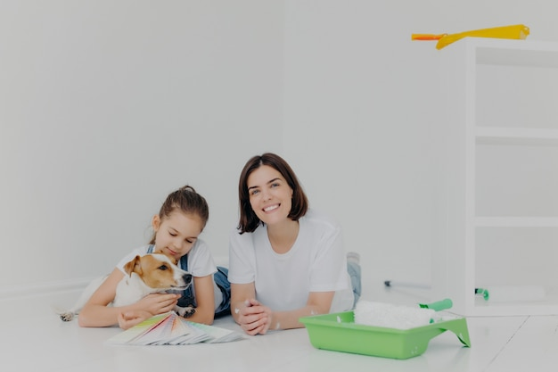 Mother and daughter with their pedigree dog lie on floor Premium Photo