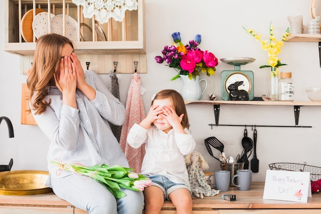 Mother and daughter with tulips covering eyes Free Photo