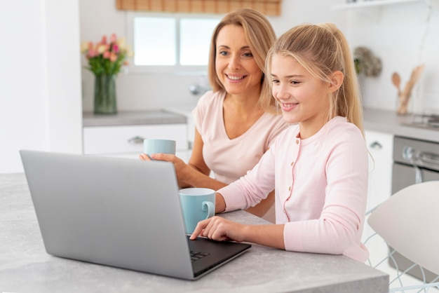 Mother and daughter working on laptop Free Photo