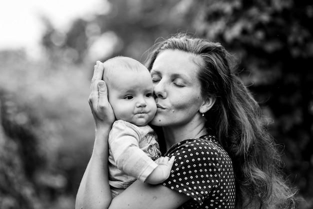 어머니는 자연에 그의 작은 아들을 포용하고 키스 프리미엄 사진