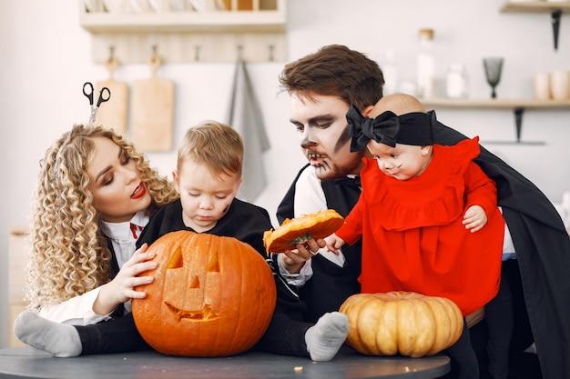 Мать, отец и дети в костюмах и макияже. семья готовится к празднованию хэллоуина. Бесплатные Фотографии