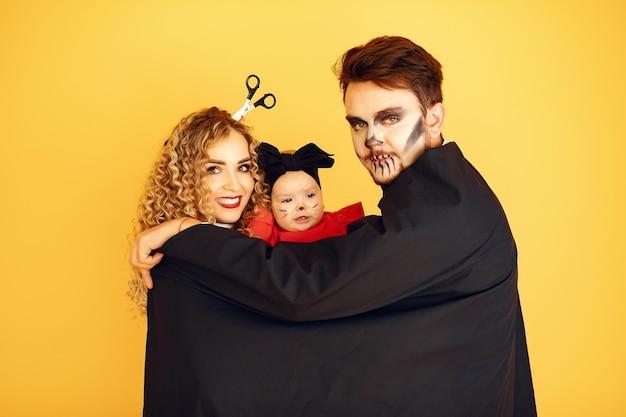 衣装と化粧の母父と子供たち。黄色の背景に立っている人。 無料写真