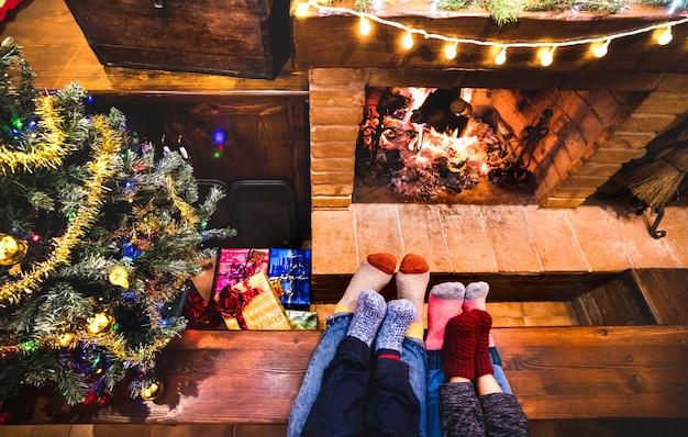 冬の居心地の良い暖炉に座っている母父と子供たち Premium写真