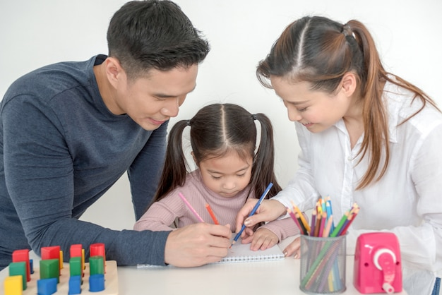 Mother and father help their daughter do homework in living room Premium Photo