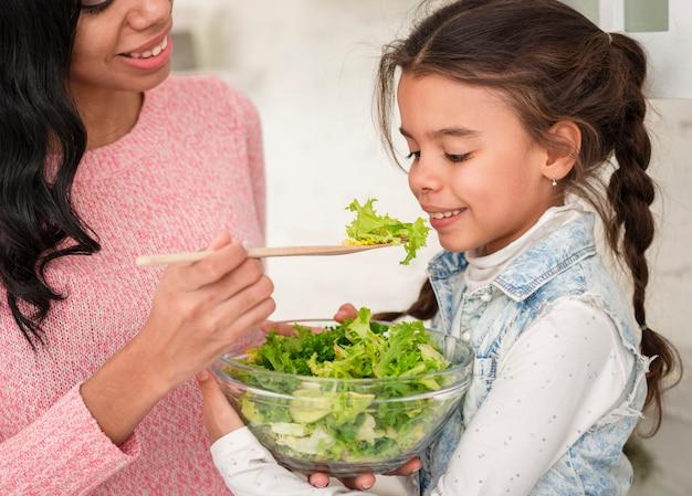 Мать кормит дочь салатом Бесплатные Фотографии