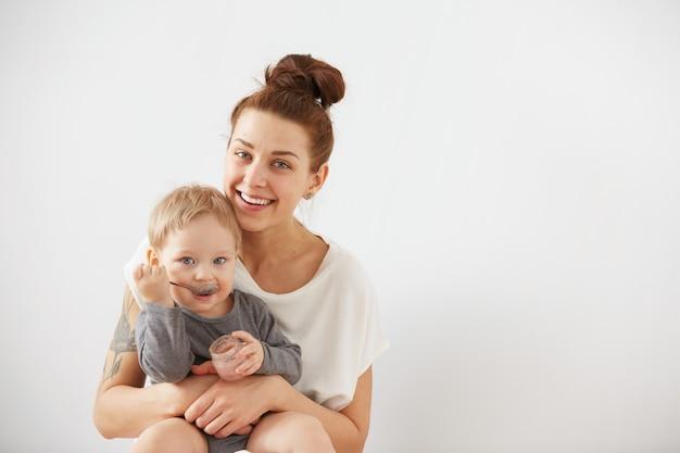 숟가락으로 그녀의 아기를 먹이 어머니 무료 사진