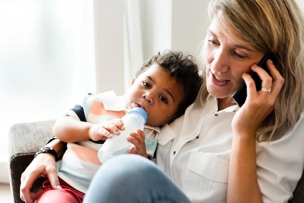 電話中に彼女の赤ちゃんを授乳する母親 Premium写真