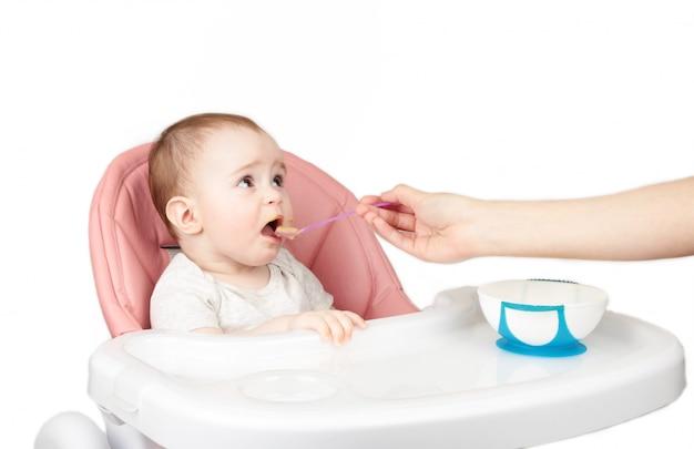 母は、白い背景で隔離の椅子に彼女のかわいい女の子を供給します。 Premium写真