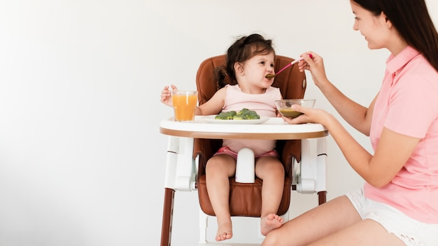 Mother feeding her cute daughter Free Photo