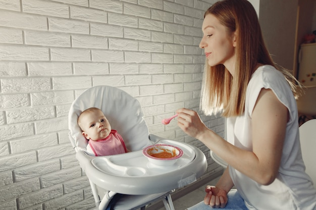 Mother feeding her little baby in a kitchen Free Photo