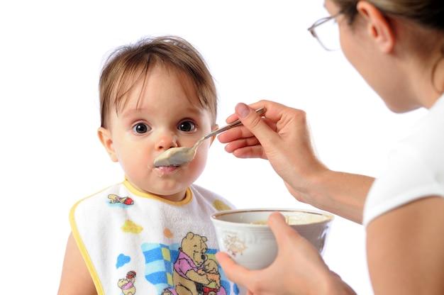 彼女の小さな女の子を養う母 Premium写真
