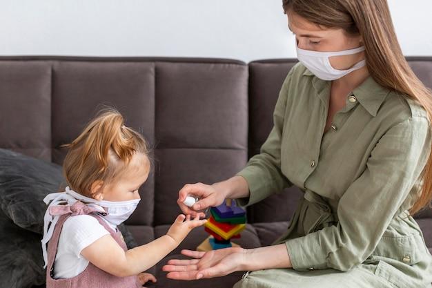 Mani disinfettanti della ragazza e della madre Foto Gratuite