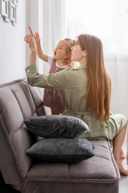 Madre e ragazza guardando la cornice Foto Gratuite