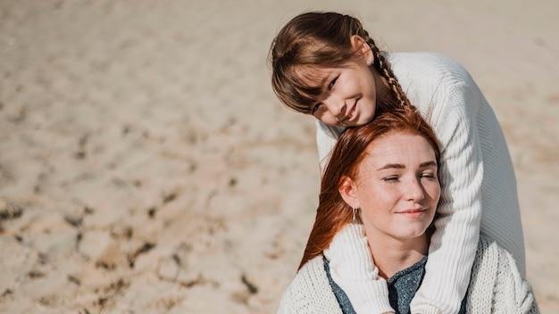 Madre e ragazza in posa in spiaggia Foto Gratuite